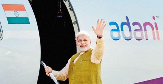 A victorious Modi arrives in Delhi on a corporate plane